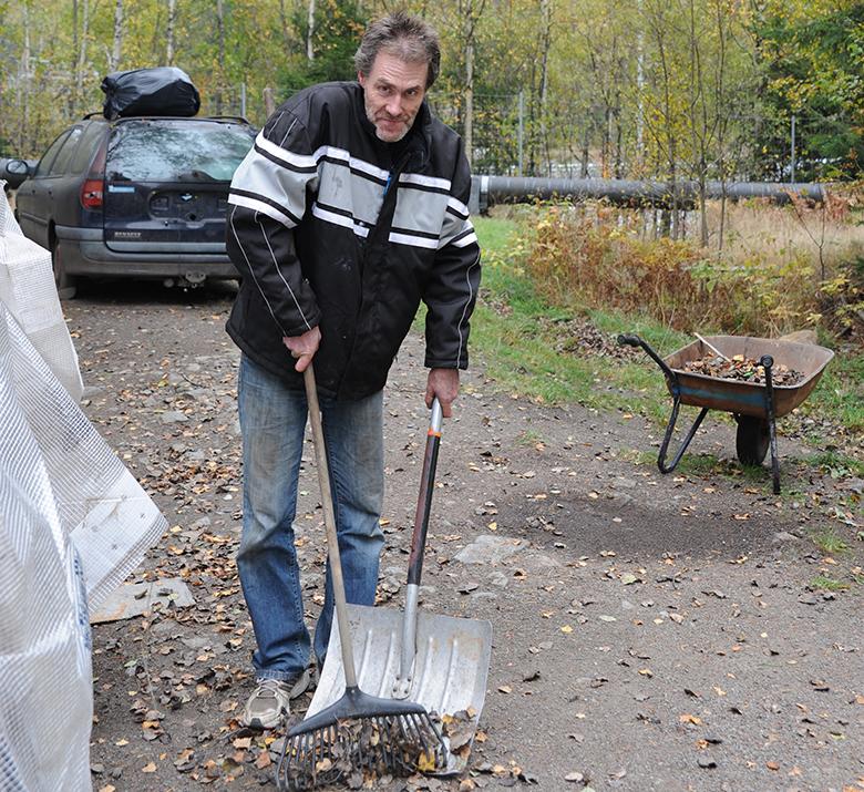 Göran passar på att kratta löv och göra fint runt husvagnen.